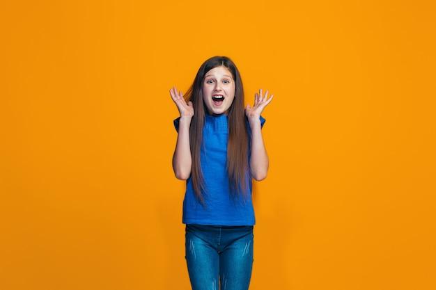 Mooi tienermeisje op zoek verrast geïsoleerd op oranje