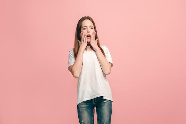 Mooi tienermeisje op zoek verrast geïsoleerd op roze muur
