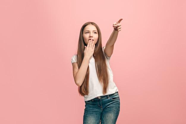 Mooi tienermeisje op zoek verrast geïsoleerd op roze
