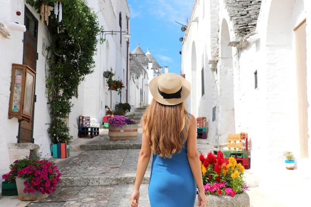 Mooi toeristenmeisje die de oude stad alberobello met de traditionele trulli-huizen in zuid-italië bezoeken