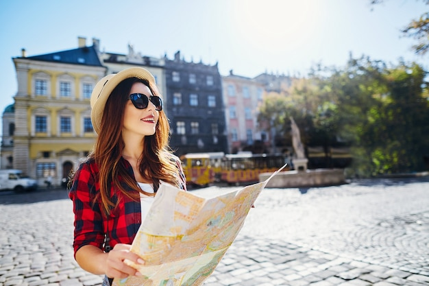 Mooi toeristenmeisje met bruin haar dat hoed, zonnebril en rood overhemd draagt, kaart bij oude europese stadsachtergrond houdt en glimlachen, reizen, portret.