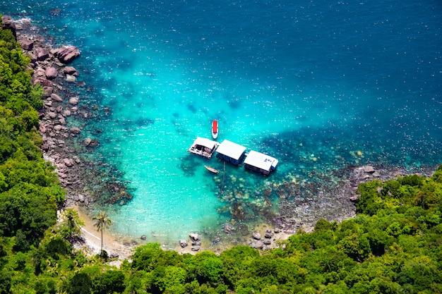 Mooi tropisch eiland met blauw duidelijk water en granietstenen. oceaankust en boten. bovenaanzicht.