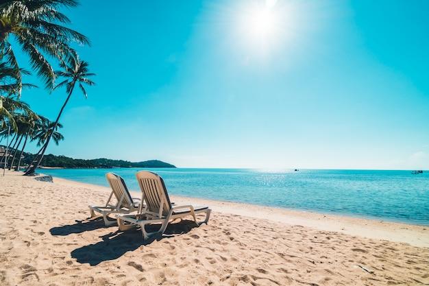 Mooi tropisch strand en overzees met stoel op blauwe hemel