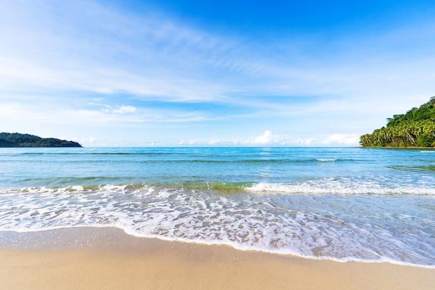Mooi tropisch strand en overzees onder blauwe hemel