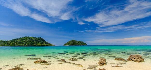 Mooi tropisch strand en zee en eiland met blauwe hemel