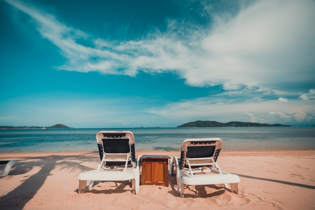 Mooi tropisch strand en zee met kokosnotenpalm en stoel in paradijseiland