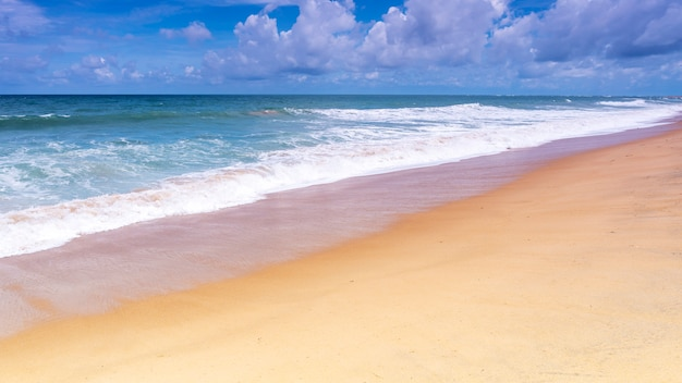 Mooi tropisch zandig strand met blauwe oceaan en blauwe hemelachtergrond en golf die op zandige kust verplettert