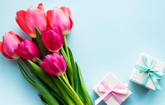 Mooi tulpenboeket en giftdozen op blauwe achtergrond