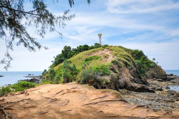 Mooi uitzicht op een rotsachtige heuvel met een witte vuurtoren