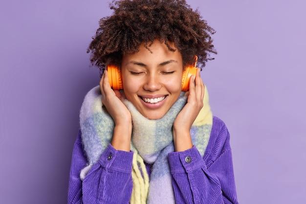Mooi uitziende gekrulde vrouw geniet van het luisteren naar aangename muziek houdt de ogen gesloten draagt een stereohoofdtelefoon met geluid van goede kwaliteit draagt een stijlvolle jas met sjaal om de nek.