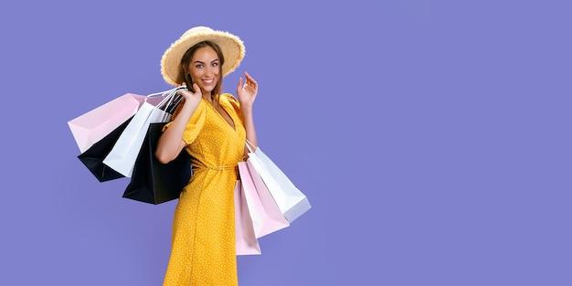 Mooi uitziende vrouw draagt nieuwe kleren terwijl ze kleurrijke pakketten op een gekleurde achtergrond grote verkopen houdt