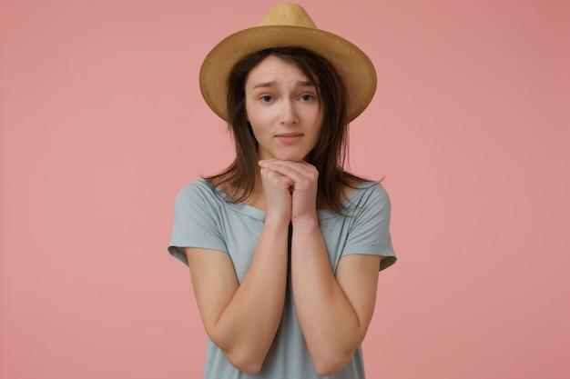 Mooi uitziende vrouw, mooi meisje met lang donkerbruin haar. het dragen van blauwachtig t-shirt en hoed. geïsoleerd over pastelroze muur