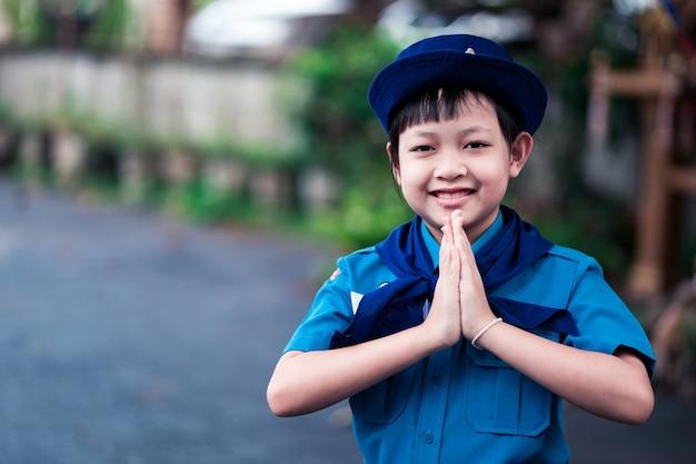 Mooi uniform verkennersmeisje steekt handen op om respect te betuigen of sawasdee met blij en glimlach
