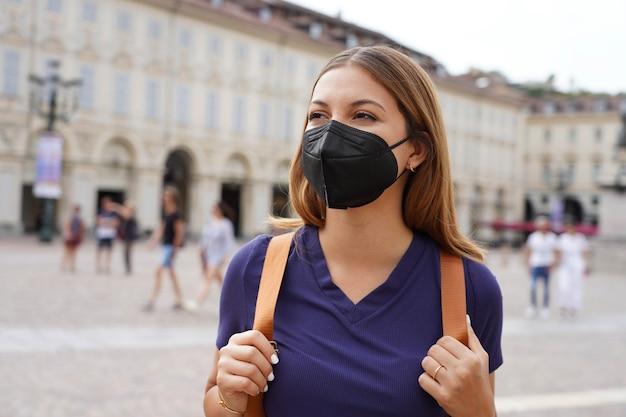 Mooi universiteitsstudentmeisje dat een beschermend kn95 ffp2 zwart masker draagt dat in stadsstraat loopt