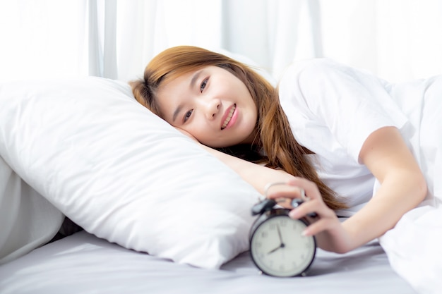 Mooi van aziatische vrouw van het portret zet wekker in ochtend uit
