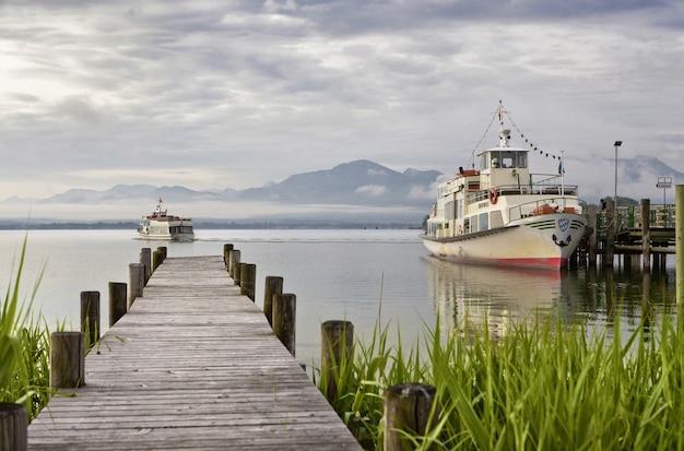 Mooi van een houten dek dat naar de zee leidt met bergen en schepen op de achtergrond