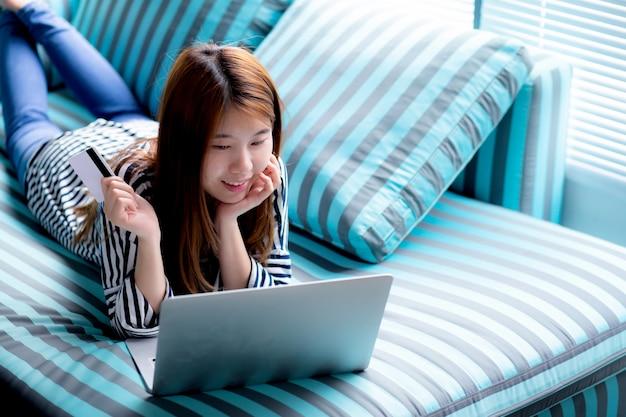 Mooi van liggende de gebruikerscreditcard van de portret jonge aziatische vrouw met laptop