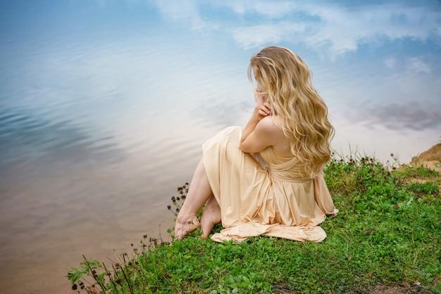 Mooi verdrietig meisje zittend op de oever van het meer in een jurk, het concept van eenzaamheid.