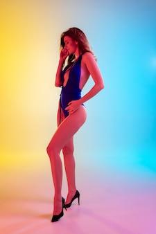 Mooi verleidelijk meisje in modieus blauw zwempak op helder gradiënt geel-blauw in neonlicht