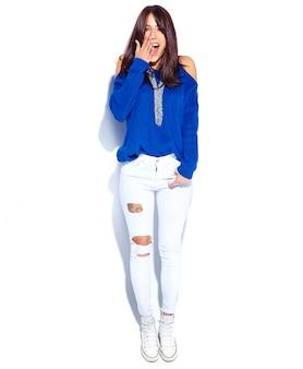 Mooi verrast hipster donkerbruin vrouwenmodel in toevallige modieuze de zomer blauwe sweater die op witte achtergrond wordt geïsoleerd. haar gezicht met de hand bedekkend, volledige lengte