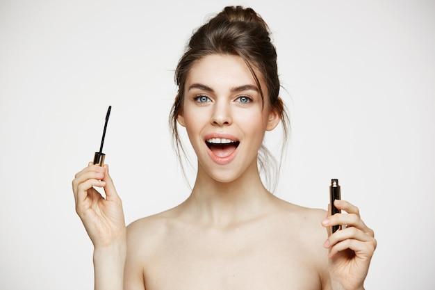 Mooi verrast meisje dat met perfecte schone huid camera met de geopende mascara van de mondholding over witte achtergrond bekijkt. gezichtsbehandeling.