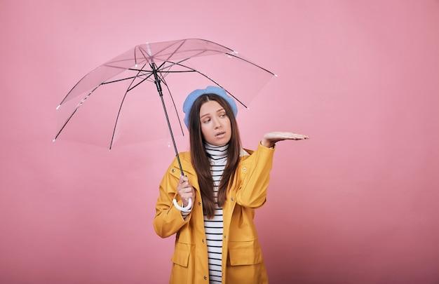 Mooi verrast meisje in blauwe baret en geel regenjasje met in hand paraplu