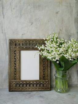 Mooi vintage frame met boeket van lelietje-van-dalen op een grijze achtergrond