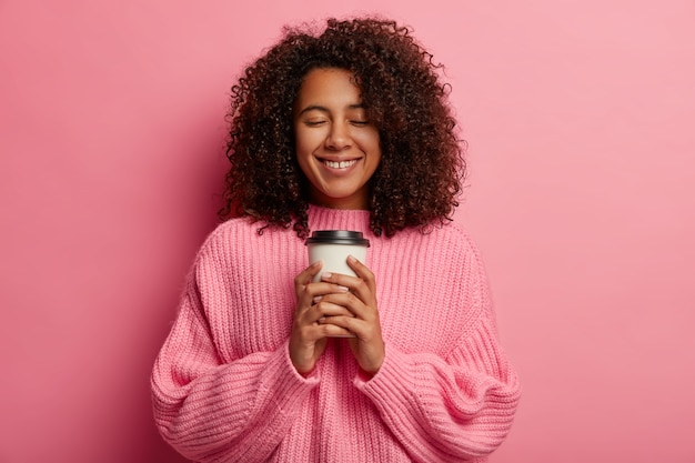 Mooi vrolijk duizendjarig meisje met zachte glimlach, houdt afhaalkoffie vast, geniet van aromatische cafeïnedrank en goede smaak