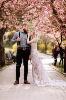 Mooi, vrolijk en schattig paar in bloeiende roze kersenbloesem, sakura tuin, knuffelen en kijken naar elkaar op een zonnige dag. lente bruiloft portret