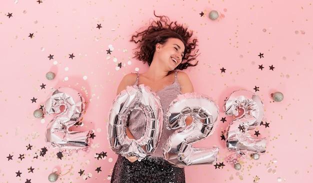 Mooi vrolijk feestelijk gekleed brunette meisje met krullend haar op een roze achtergrond met zilveren ballonnen uit de nummers 2022, nieuwjaarsfeestconcept.