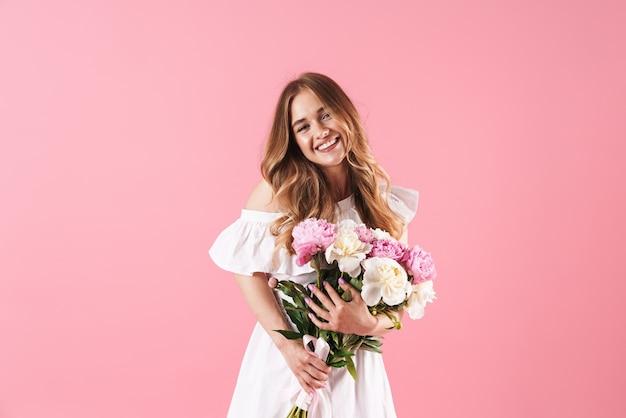 Mooi vrolijk jong blond meisje met een zomerjurk die geïsoleerd over een roze muur staat en een boeket pioenrozen vasthoudt