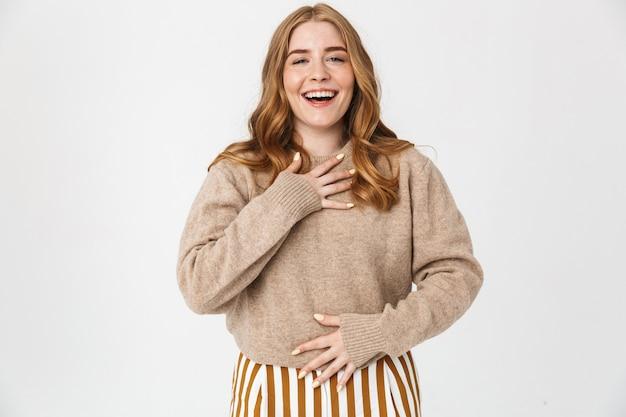 Mooi vrolijk jong meisje met lang blond krullend haar met een trui die geïsoleerd over een witte muur staat, lachend