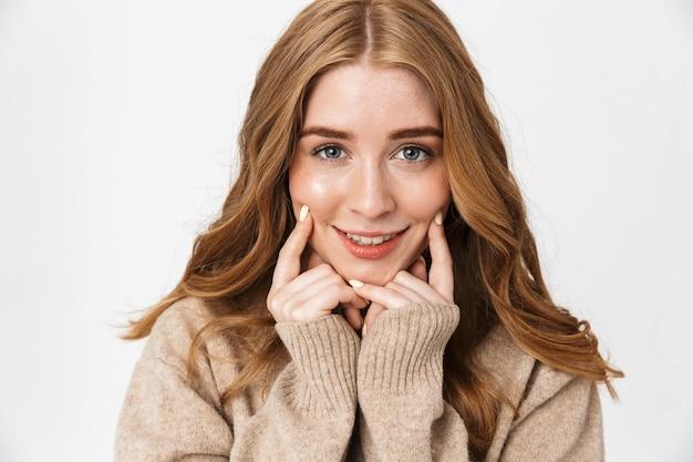 Mooi vrolijk jong meisje met lang blond krullend haar met een trui die geïsoleerd staat over een witte muur