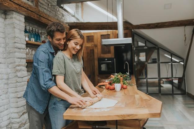 Mooi vrolijk jong paar kokend diner samen en het hebben van pret bij rustieke keuken