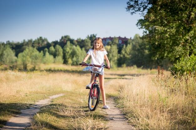 Mooi vrolijk meisje fietsten in de weide op zonnige dag