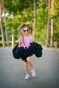 Mooi vrolijk meisje in een pluizige tutu rok in zonnebril met een lange staart van haar danst en glimlacht