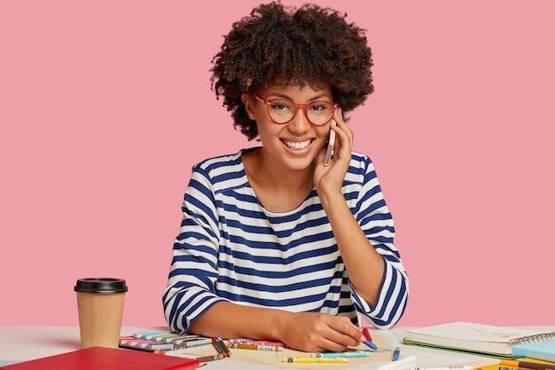 Mooi vrolijk studentenmeisje poseren bij het bureau tegen de roze muur