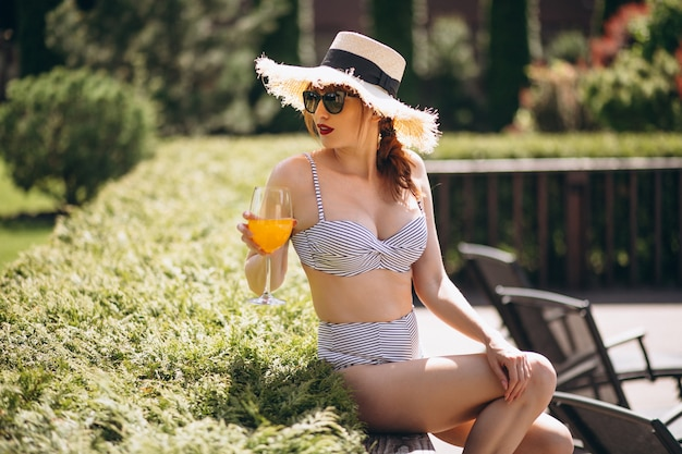 Mooi vrouw het drinken sap in zwemmend kostuum