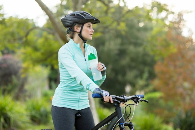 Mooi vrouwelijk fietser drinkwater in bos