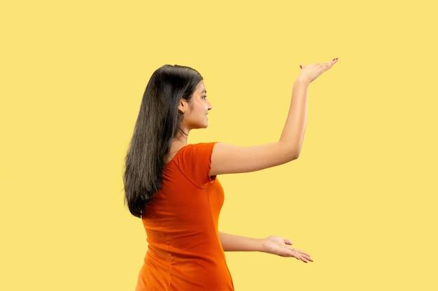 Mooi vrouwelijk geïsoleerd portret van halve lengte. jonge emotionele indische vrouw die in kleding een plaats voor uw advertentie houdt. negatieve ruimte. gelaatsuitdrukking, concept van menselijke emoties