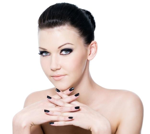 Mooi vrouwelijk gezicht met de make-up van het manieroog en zwarte manicure