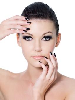 Mooi vrouwelijk gezicht met zwarte oogsamenstelling en zwarte manicure