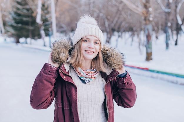 Mooi vrouwelijk glimlachend portret. portret van het gelukkige meisje dat besneeuwde winterkleren draagt