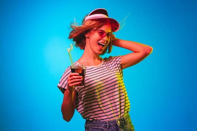 Mooi vrouwelijk half-lengteportret dat op blauwe neonlichtstudio wordt geïsoleerd