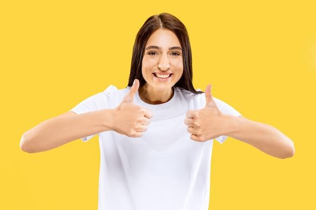 Mooi vrouwelijk half-lengteportret dat op gele studio wordt geïsoleerd