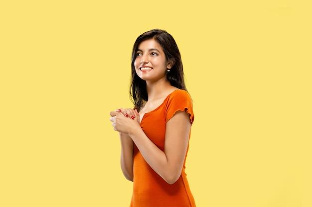 Mooi vrouwelijk half-lengteportret dat op gele studioachtergrond wordt geïsoleerd. jonge emotionele indiase vrouw in jurk verbaasd en blij. negatieve ruimte. gelaatsuitdrukking, concept van menselijke emoties.
