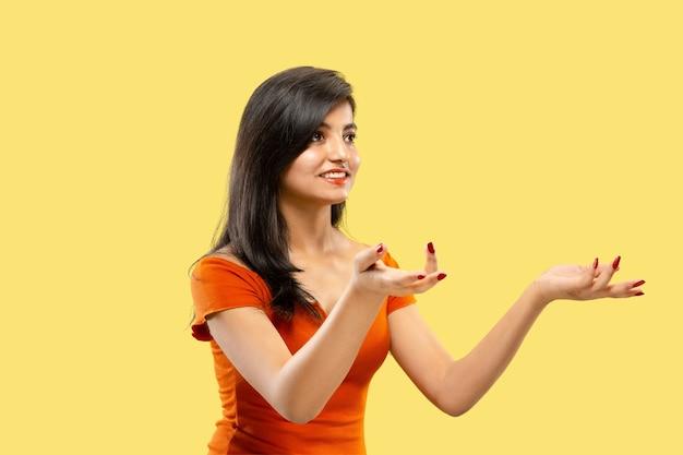 Mooi vrouwelijk half-lengteportret dat op gele studioachtergrond wordt geïsoleerd. jonge emotionele indiase vrouw in jurk wijzen en tonen. negatieve ruimte. gelaatsuitdrukking, concept van menselijke emoties.