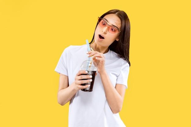 Mooi vrouwelijk half-lengteportret dat op gele studioachtergrond wordt geïsoleerd. jonge glimlachende vrouw. gelaatsuitdrukking, zomer, weekend, resortconcept. trendy kleuren.