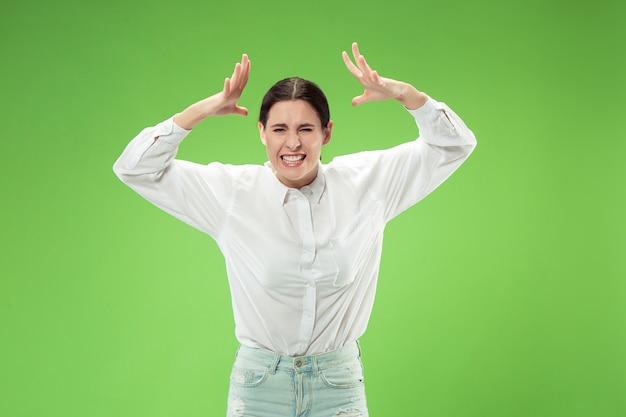 Mooi vrouwelijk half lengteportret dat op groene muur de jonge emotioneel verraste vrouw wordt geïsoleerd