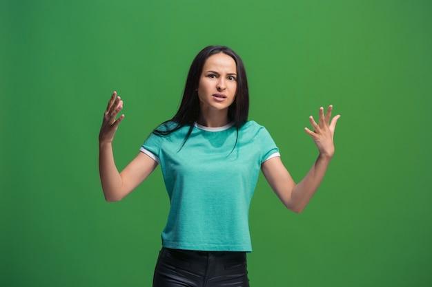 Mooi vrouwelijk half-lengteportret dat op groene studio wordt geïsoleerd